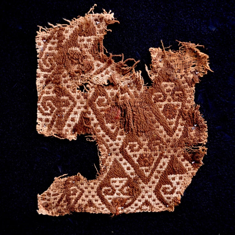 Earth tones pre-Columbian textile fragment with abstract embroidered figures. This piece is framed in a black shadowbox.