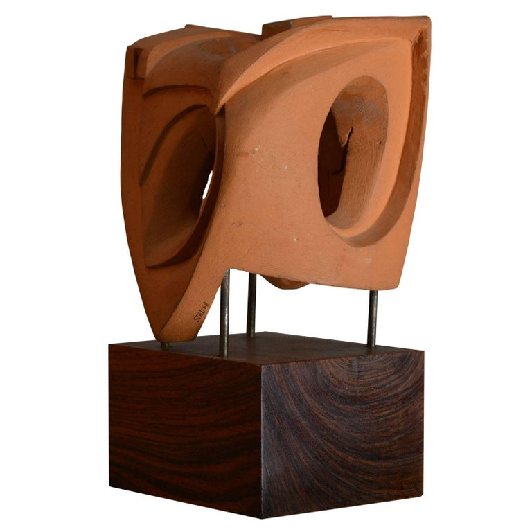 The terracotta sculpture on an olive wood base is signed STAD 1968.