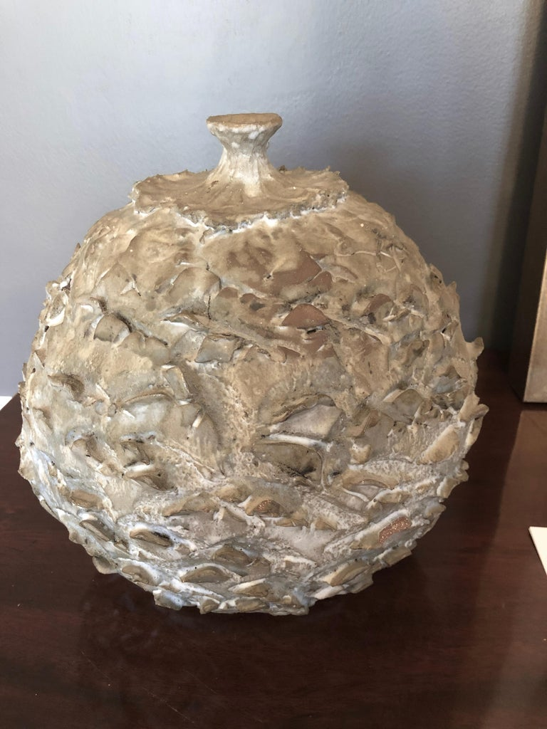 Abstract textured ceramic vessel having a grey to white abrash effect.