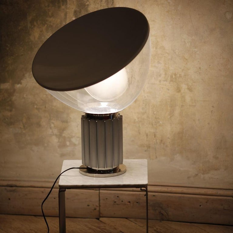Italian modern 'Taccia' table lamp designed by Achille Castiglioni for Flos in the 1960s. The aluminum and polished steel metal base is topped with an inverted glass bowl diffuser shade and a white aluminum shade. Makers label on the inside of the