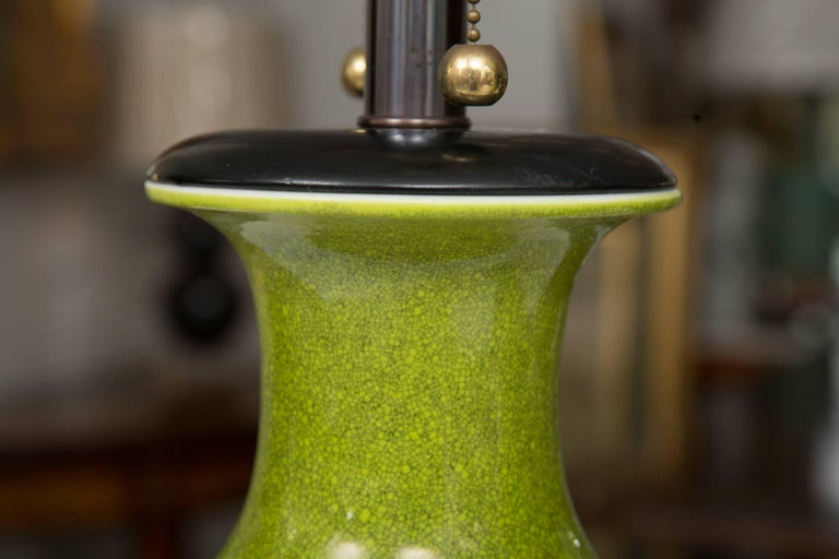 This near pair of 'acid' green baluster shaped vases have been converted to table lamps. The lamps are capped with wood and are raised with a triple stepped bases. The lamps offer a stunning accent to ones interior. 20th century.