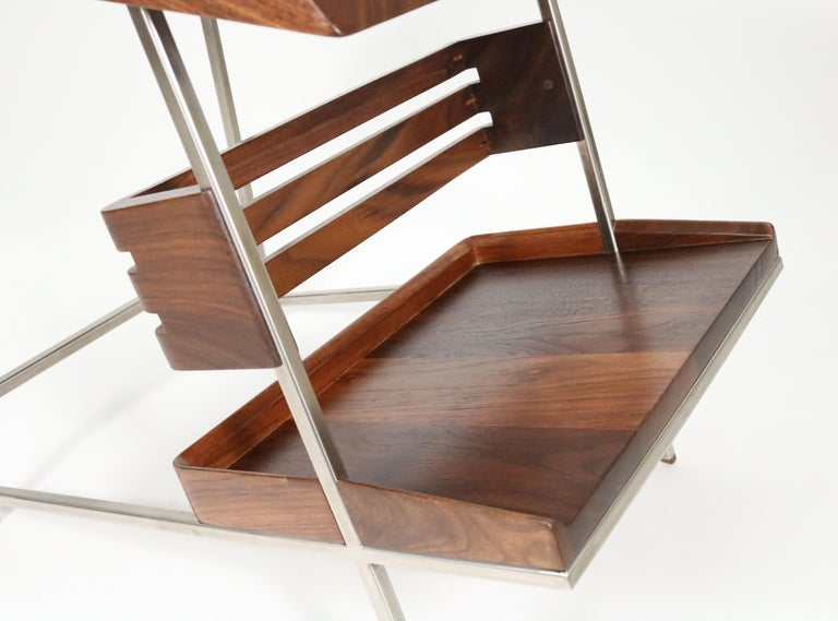Form married to function in walnut and padauk in this handsomely modern side table by Boulder, Colorado designer Alexander Giray.   The floating shelf provides display of your favorite books, while drawing your eye to the table's unique design and