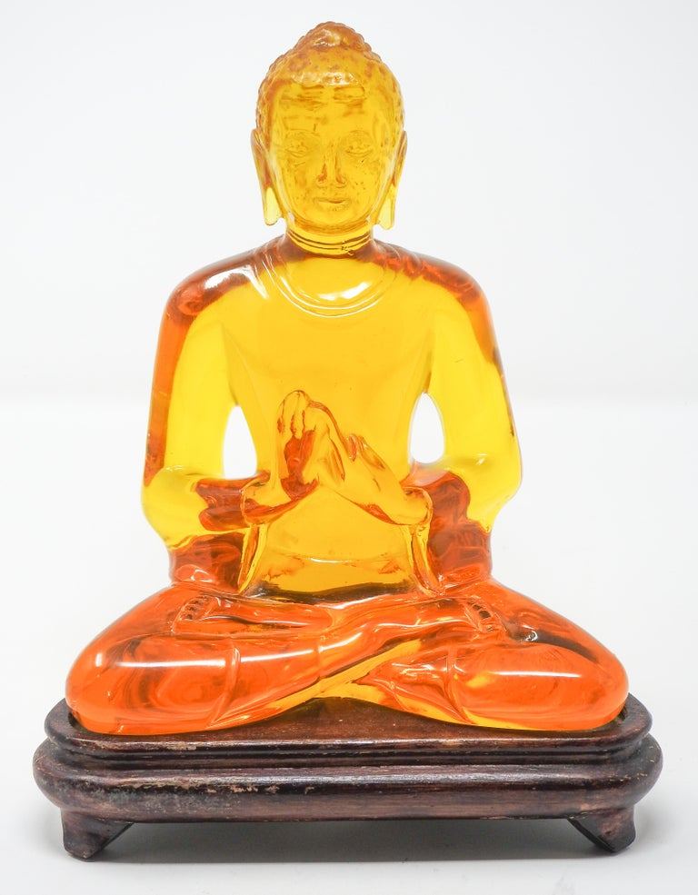 Offering this beautiful acrylic amber Buddha statue. The statue sits on a wooden base.