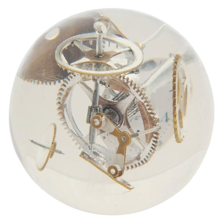 Resin lucite sphere with exploded watch parts. Medium scale cast acrylic table sculpture with incased watch elements, including gears and clock face. Sold with circular clear acrylic 2 inch stand.