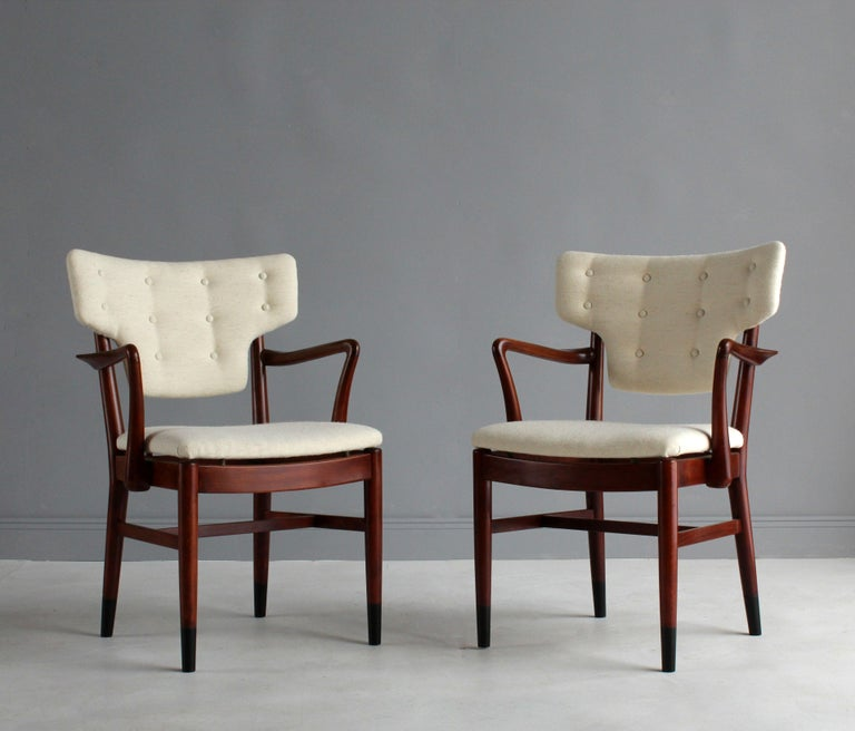 A pair of early modernist side chairs or armchairs attributed to Danish architects Acton Bjørn & Vilhelm Lauritzen, Denmark, 1940s. Frame of superb Danish cabinet maker quality in sculpted stained beech, original dark stained cap feet. Reupholstered