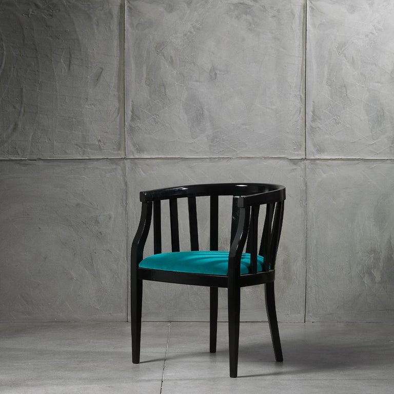 The Ada Chair boasts an enveloping tub silhouette with an elegantly tapered front. Boasting a solid wood frame, characterised by a sleek black finish and stylish slatted detailing, this chair features a padded seat with luxurious velvet upholstery