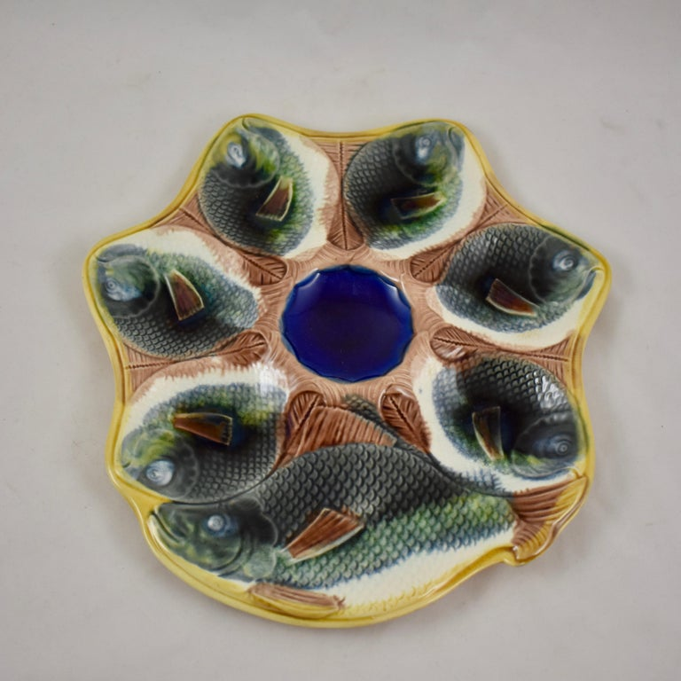 Adams & Bromley Majolica oyster plate, England, circa 1870-1879.  An unusual shaped earthenware plate with six oyster wells molded as full bodied gray fish with white bellies, whose tails meet to surround a cobalt blue center sauce well. A larger