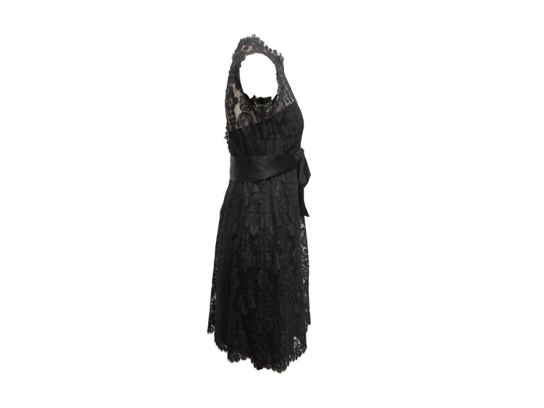 Product details: Vintage black lace sleeveless dress by Adele Simpson. Crew neck. Partially sheer bodice. Satin bow at waist. 32