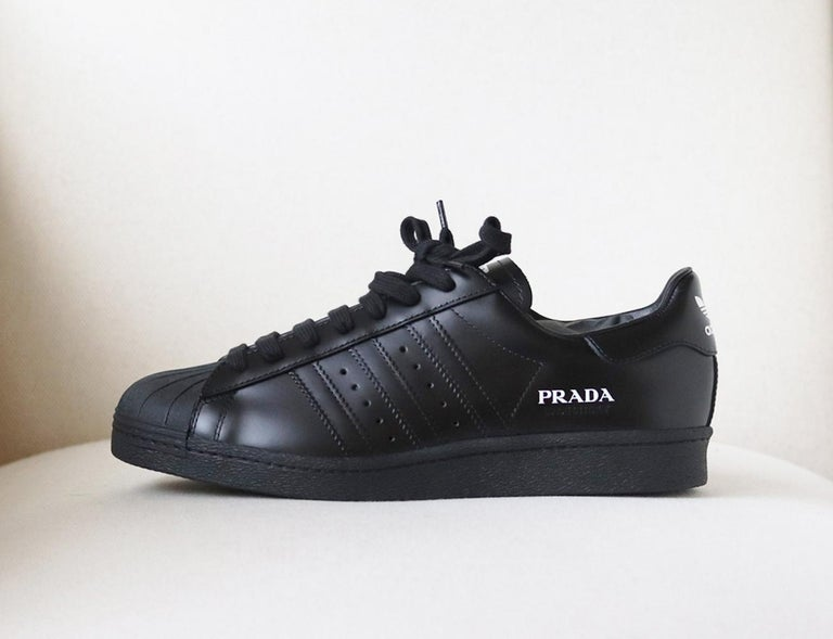 adidas Originals' 'Superstar' sneakers are designed in collaboration with Prada. They've been made in Italy from polished black leather printed with both labels' logos in contrasting white. Rubber sole measures approximately 25mm/ 1 inch. Black