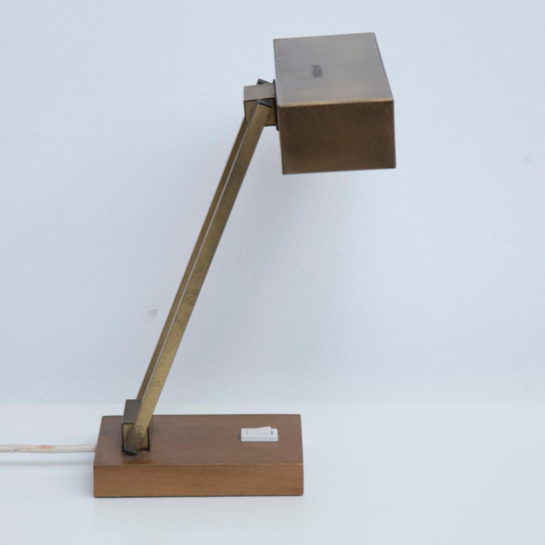 Beautiful desk lamp produced in the 50s. The lamp is adjustable and made of brass and shows a lovely patina. Very nice sculptural lines through the double adjustable arm on a brass base.