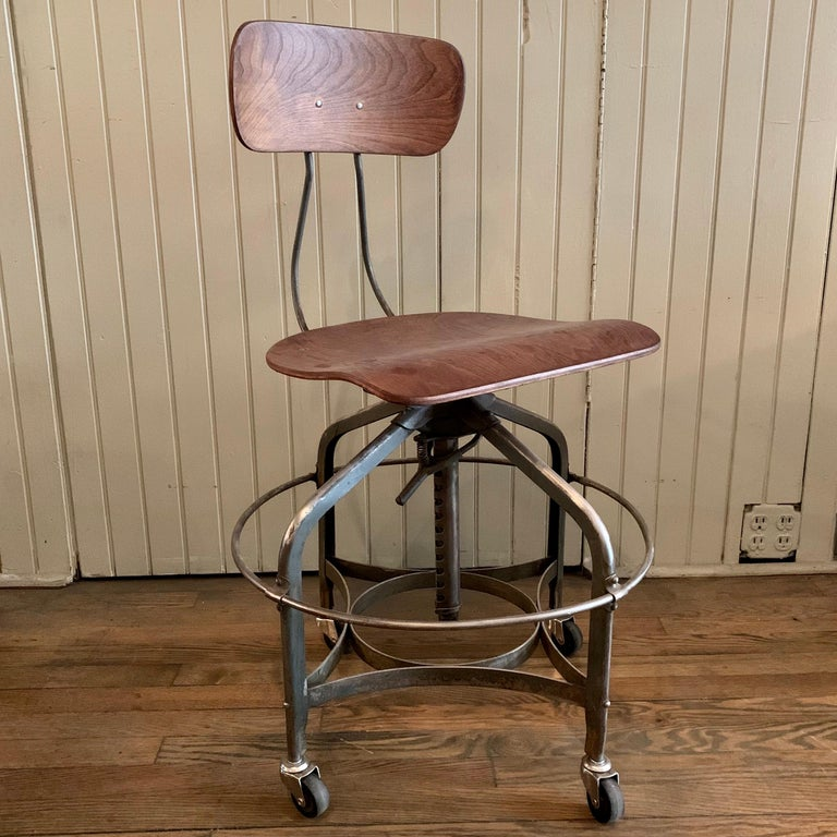 Industrial, adjustable, rolling, factory stool by Toledo Metal Furniture Co., features a brushed steel frame with wide 20 inch diameter ring footrest and oak seat and back. The height adjusts from 20 - 28 inches. The seat measures 16 wide x 14 deep.
