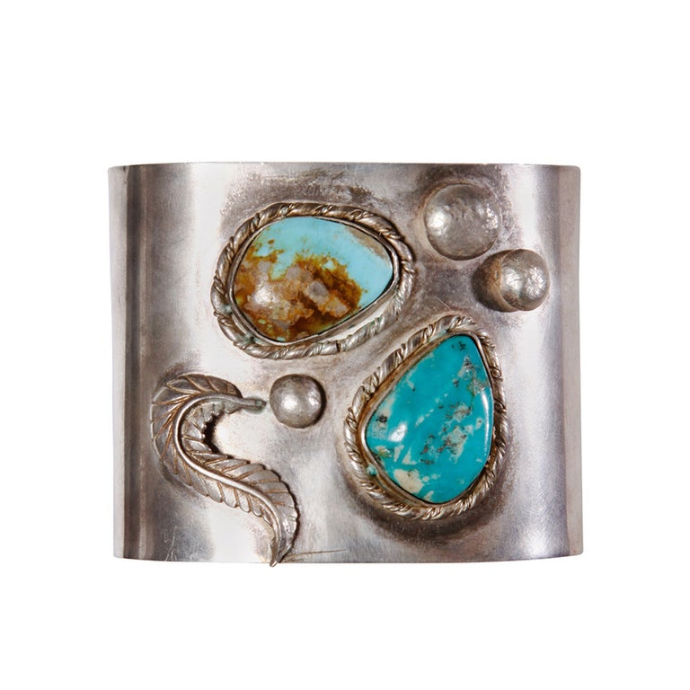 Gorgeous hand-made vintage sterling silver cuff with two large turquoise stones. This is a Native American artisan piece and was engraved,