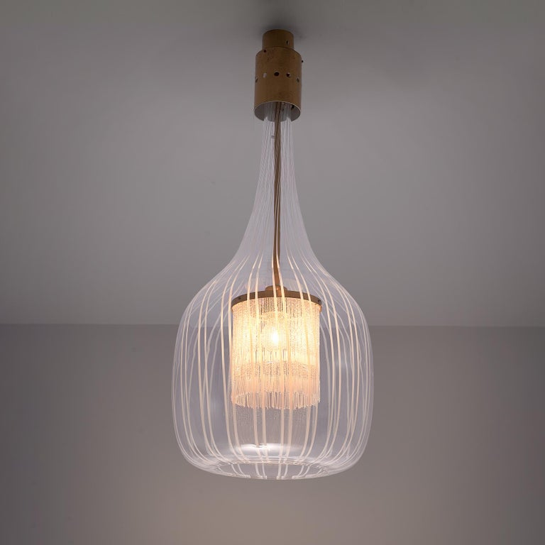 Angelo Brotto for Esperia, pendant light, glass, brass, Italy, 1970s  Angelo Brotto's design is elegant by all means. On a brass fixation hangs a glass latern that is decorated with vertical lines. The handblown Murano glass shows true