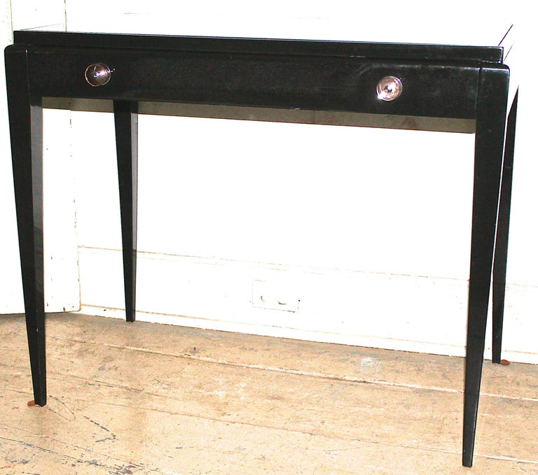 Simple tapered lines, one narrow draw with amazing Lucite and chrome pulls. The desk surface is a black glass inset. In very pristine condition being recently re lacquered.