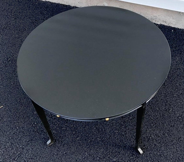 Adnet style iron and brass low table, of circular form with brass ball frieze, raised on splay legs.