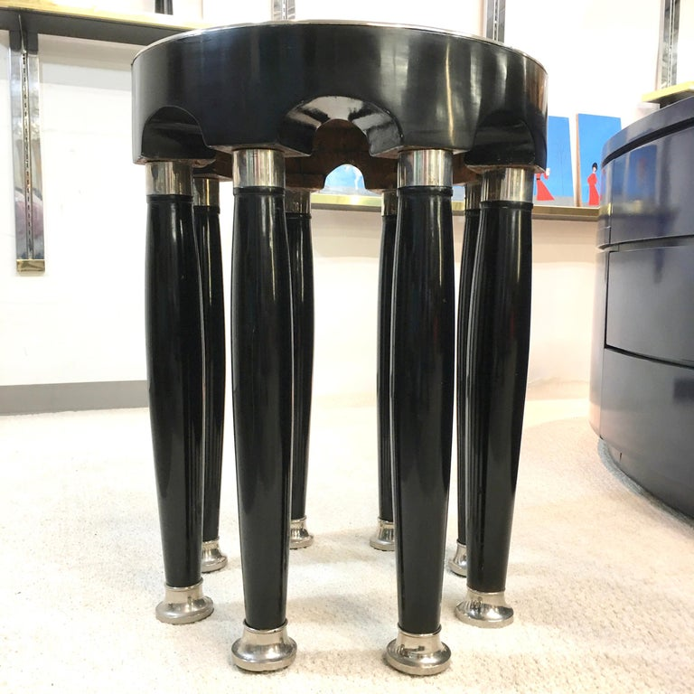 An eight-columned avant-garde round table attributed to Adolf Loos and executed by the Viennese firm of Friedrich Otto Schmidt.  Polished black enamel over hardwood and veneer with polished chrome cuffs and sabots. Adolf Loos used variations of