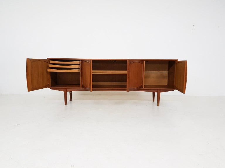 Scandinavian Modern teak credenza or sideboard by Adolf Relling & Rolf Rastad for Bahus, Norway 1960s.  This Scandinavian Modern sideboard form Norway is entirely made of teak. It has 4 doors with beautiful solid teak inlays. Inside the cabinet