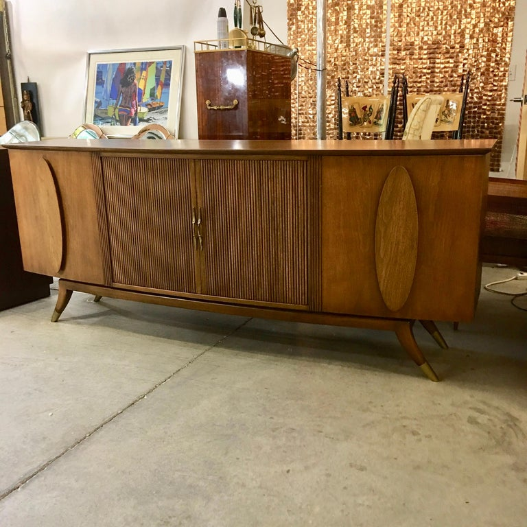 Long bow-fronted credenza in walnut with two cabinet doors and four drawers behind sliding tambour doors with brass pulls. The top two drawers are lined and divided for silverware. The two side cabinets each have two horizontal adjustable shelves.