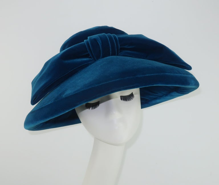 A wide brimmed velvet hat by Adolfo in a lush peacock or teal blue.  Festooned at the band with a large bow and designed with a mushroom style shape both framing the face and also allowing for an incognito look when worn with large shades ... a la