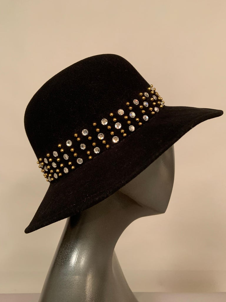 This sparkling hat will add a lot of glamour to any outing or outfit!  The traditional black felt fedora has been transformed by the addition of three rows of prong set rhinestones and faceted brass studs in place of a hatband.  The hat is all wool