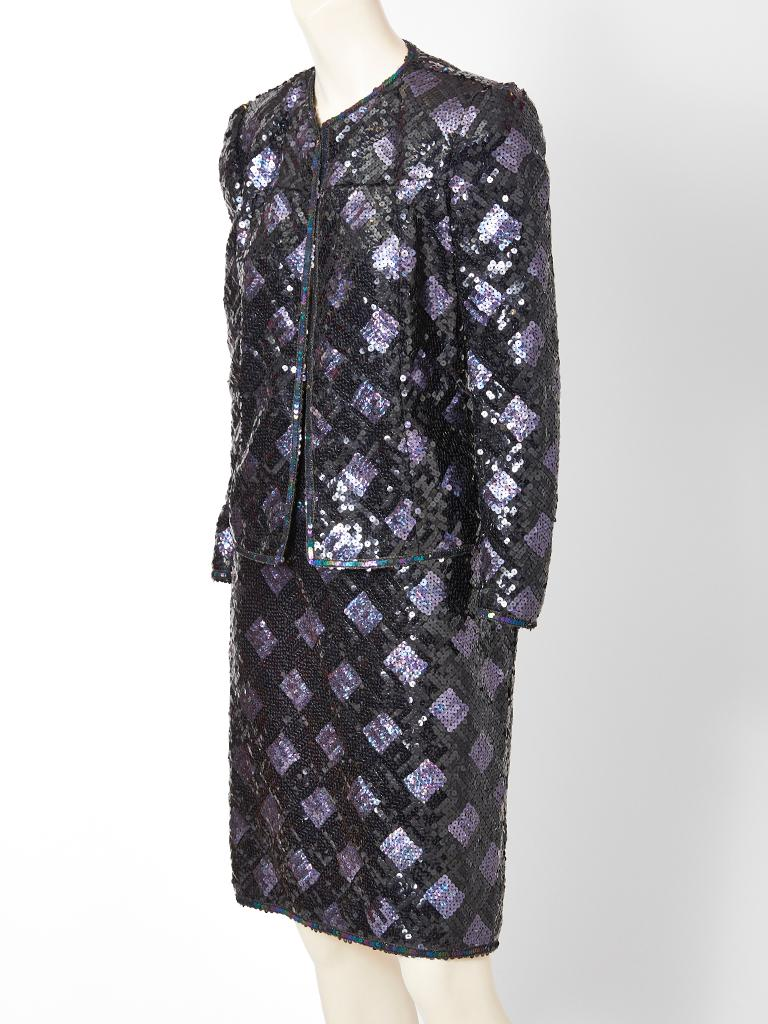 Adolfo, dinner suit, encrusted in black and purple iridescent sequins, that form a diamond pattern. Jacket is fitted with a jewel neckline that ends below the hip. Skirt is straight.