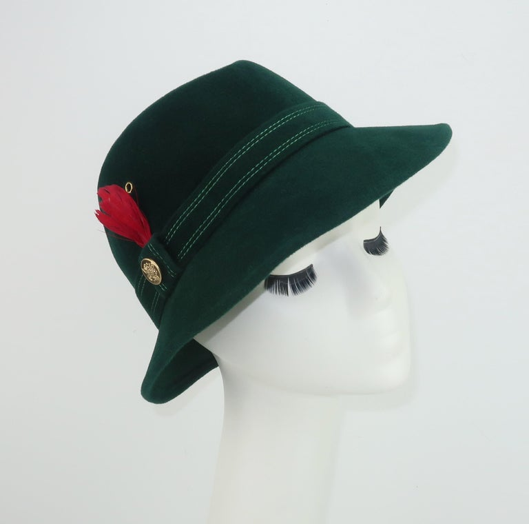 Add a distinctive Alpine touch to your tweeds and woolens with this utra stylish C.1970 Adolfo II green wool felt hat embellished with a red feather and gold button completing the classic Tyrolean look.  A menswear style perfect for accessorizing a