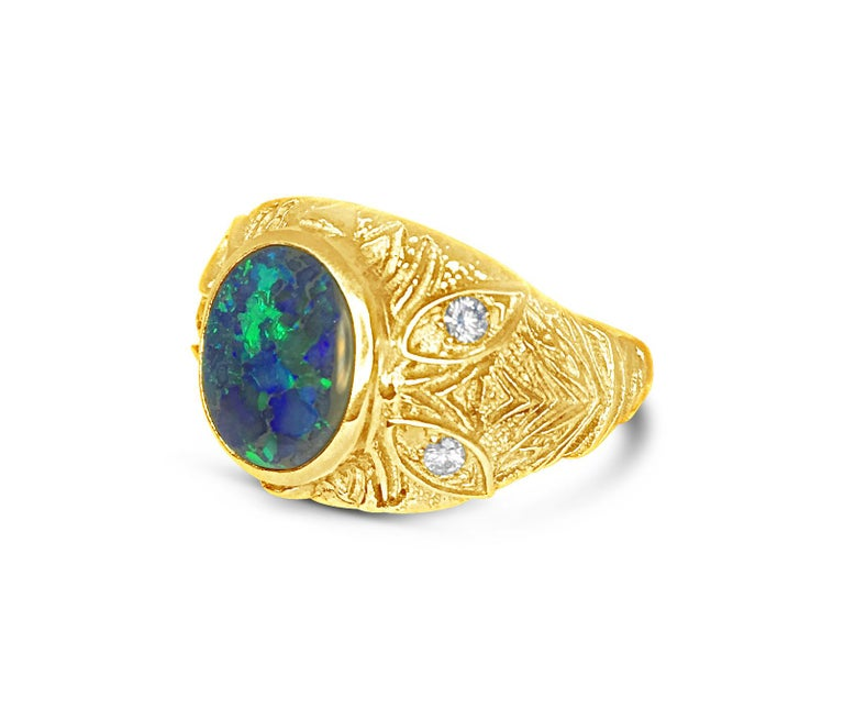 Radiantly textured gold sets off the black Australian Opal play of blue and green colors. The design of the A'donna collection lets the Diamonds shine as accents in this beautiful ring designed by Katherine LeGrand of Aspen, Colorado.  18kt Yellow