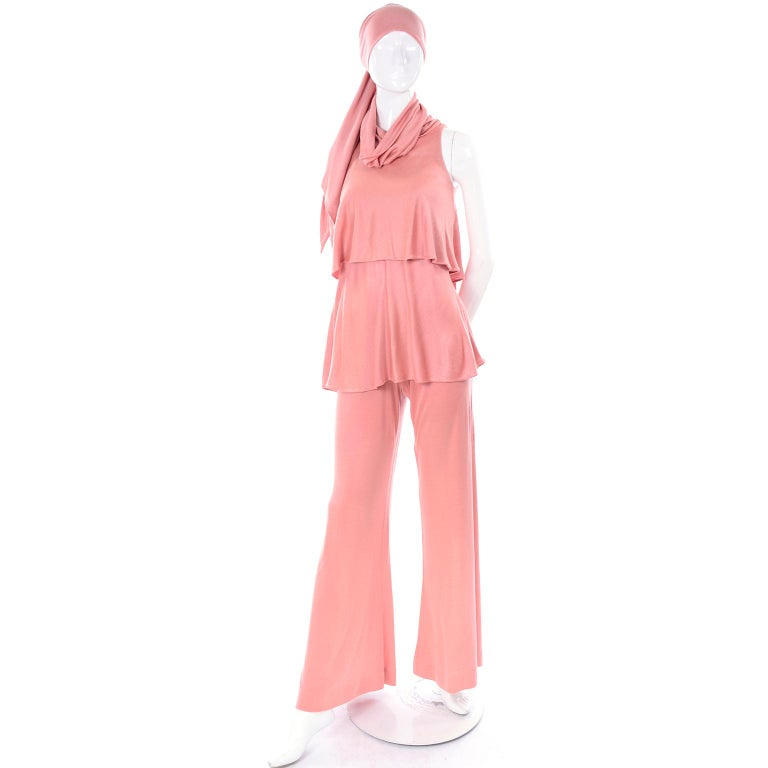 This is a glamorous vintage Adri coral pink jersey outfit, with a sleeveless turtleneck top, wide leg stretch pants and matching sash!  The designer was known for her free flowing garments made of Italian imported fabrics. The turtleneck has enough