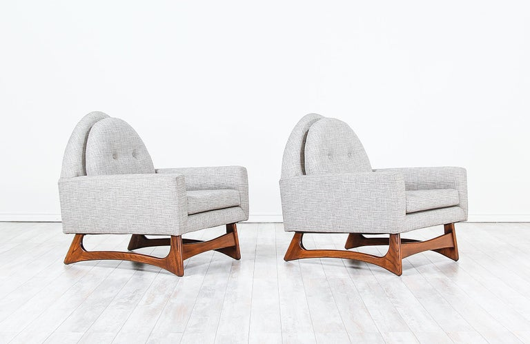 A pair of lounge chairs designed by Adrian Pearsall for Craft Associates in the United States, circa 1960s. These lounge chairs feature a sculpted walnut wood base with solid stretchers that create a durable foundation for lasting comfort. The loose