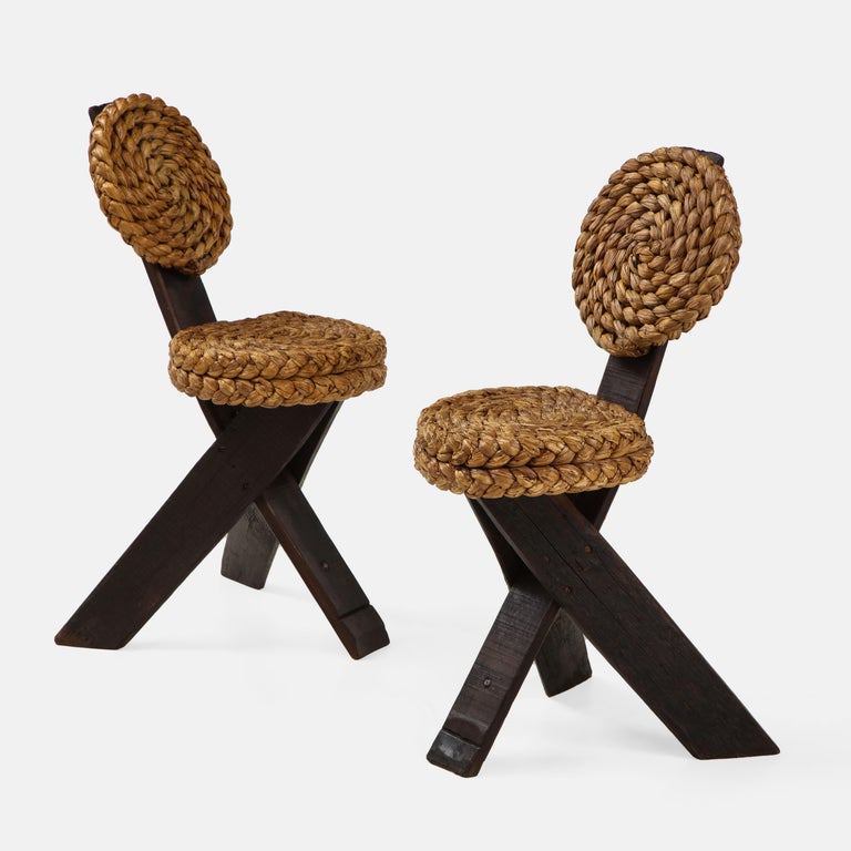 Adrien Audoux and Frida Minet rare pair of brutalist side chairs with braided rope backs and seats on stained wood frames ending in tripod legs. These unusual sculptural chairs are a typical Audoux et Minet modernist design incorporating elements of