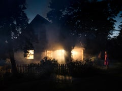 Sevilles House, Photograph of Woman in Pink in Front of House with Glowing Light