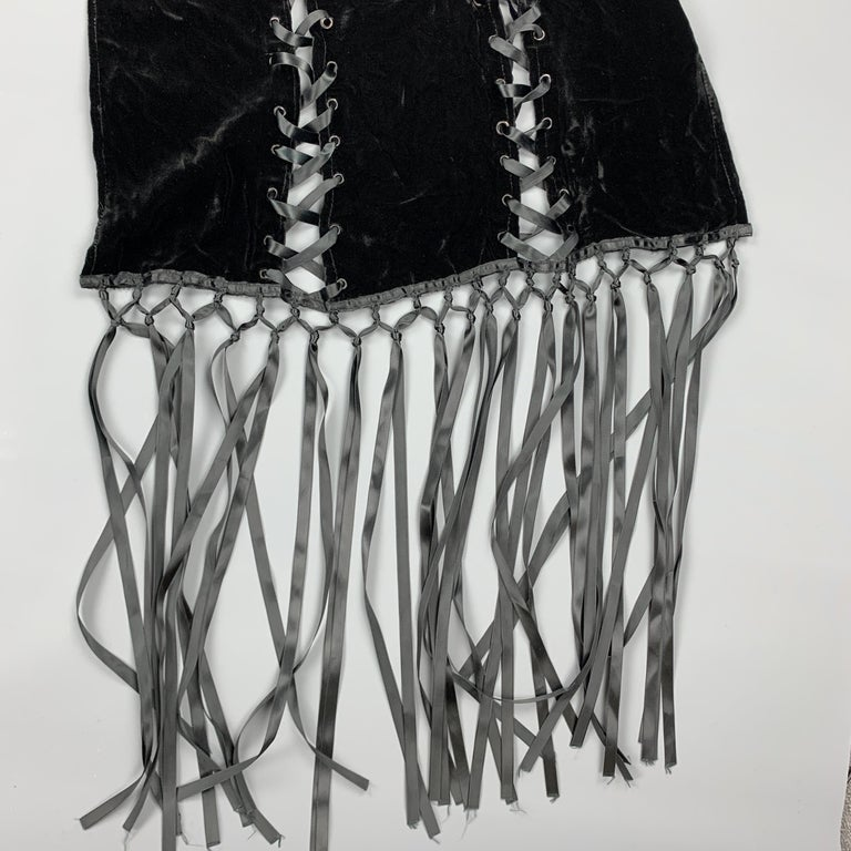 ADRIENNE LANDAU scarf comes in black velvet with a ribbon laced cutout grommet panels and long seventeen inch woven fringe trim.   Good Pre-Owned Condition.  Length: 84 - 108 in. Width: 21 in.