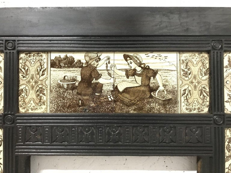 English Aesthetic Movement cast iron fire insert in the style of Thomas Jeckyll with the original aesthetic movement tiles depicting children picking flowers and making daisy chains to the top with two boys to the left taking birds eggs and two