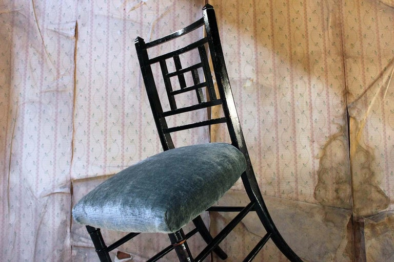 The ebonized reeded frame with a pierced geometric panel lattice back to peaked finials, on four ring turned legs, the sprung seat upholstered in a jewel turquoise velvet, with one rear leg stamped '50683'. surviving from the late Victorian period