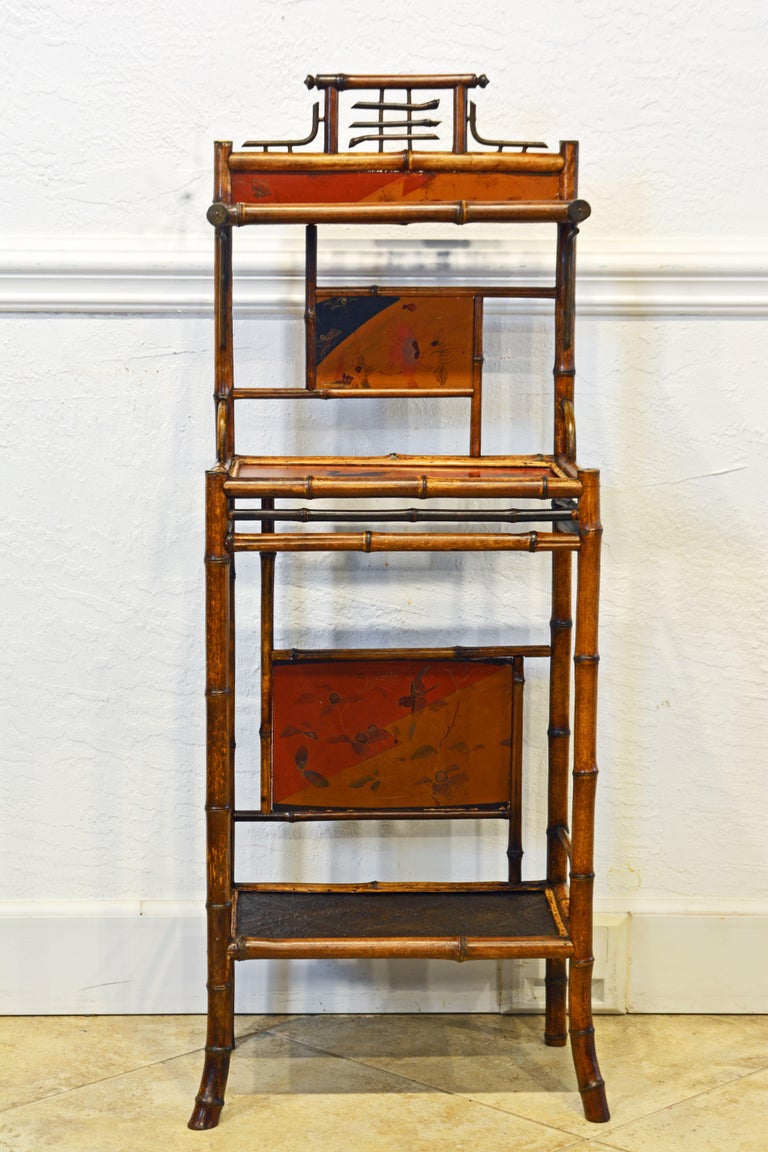 An English Aesthetic Movement chinoiserie style three-tier étagère or stand consisting of a bamboo framework with lacquered and decorated surfaces and panels.