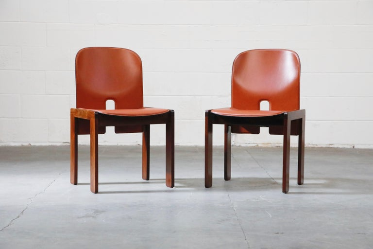 This highly collectible and simply incredible pair of rust-orange colored saddle leather and Rosewood model 121 chairs are by Afra and Tobia Scarpa for Cassina. This particular pair is a perfect collectors set due to several reasons detailed below,
