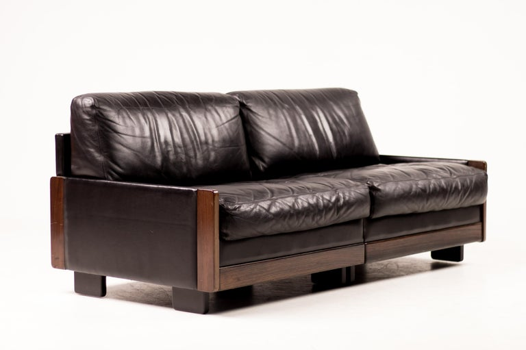 Sophisticated sofa manufactured by Cassina in 1966, designed by Afra and Tobia Scarpa.  Mahogany frame with black leather covering the sides and back, seat and back cushions.  Base in black painted wood.