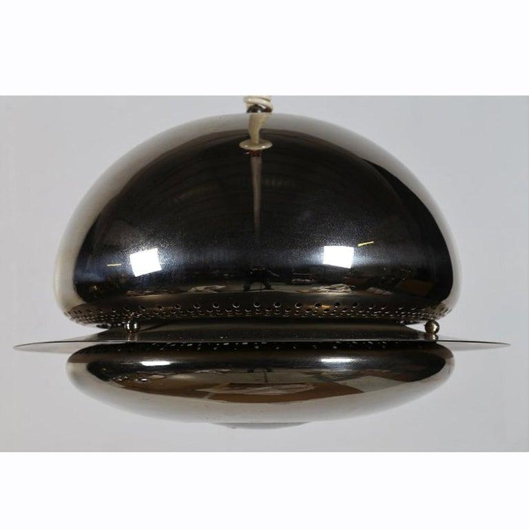 A spherical brass pendant light. Manufactured by Flos. Italy. 1960s.  Literature Domus 395, October 1962, p.48  Ottagono 1, April 1966, p. 91  Giuliana Gramigna, Repertorio 1950-2000, Allemandi, Torino 2003, p.90.  Note One pendant light in the