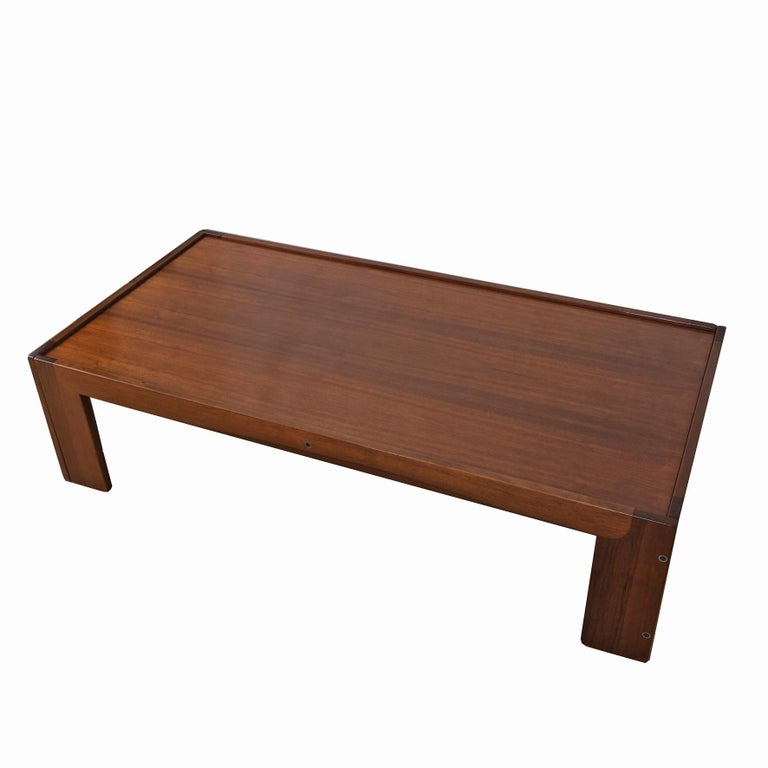 A rectangular walnut low table, the top plate rested on the frame supported by four rectangular feet. Manufactured by Cassina. With manufacturer's label underneath. Italy. 1960s.  Provenance Private collection  Literature Domus 453, agosto