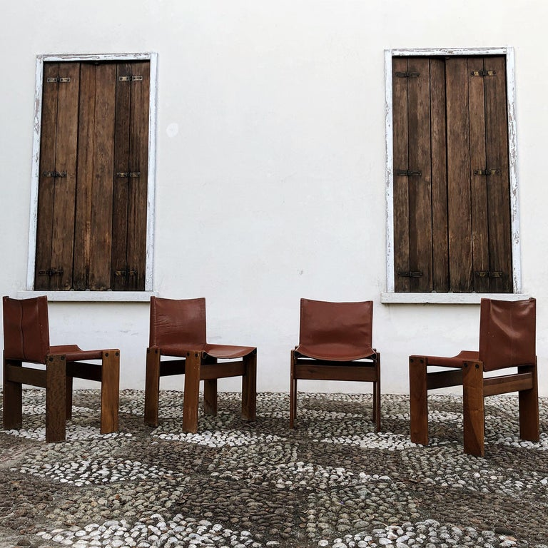 Afra & Tobia Scarpa, 4 monk dining chairs, walnut and bricky leather, Italy, 1973. Interesting is the 'flat' shape of this chair where the designer has chosen to place the legs cross-angled. This decision gives the chair the appearance of being