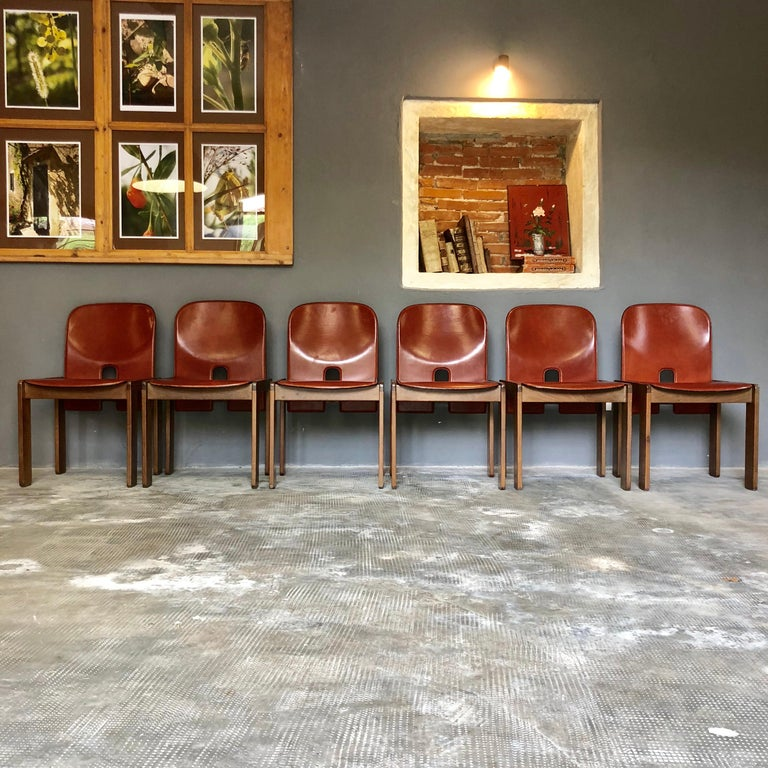 """Set of six """"121"""" chairs by Afra & Tobia Scarpa. Reddish-brown leather original upholstery. The model 121 chair was produced by Cassina's employees molding brown leather covered plywood and a base of Italian walnut. The chair is broken down to its"""