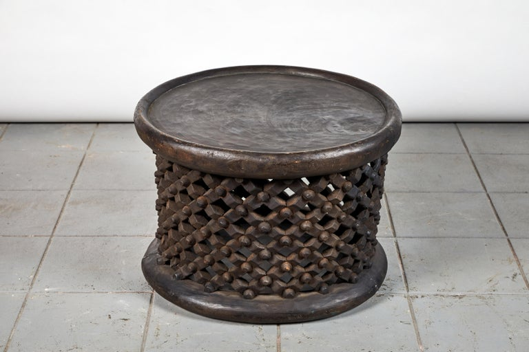 A Cameroon wood drum table with pierced and carved lattice base. The size and height is great to use as a stool, side table, or occasional table. The lattice work on the bench is in good condition, however, due to the inherent nature of solid wood