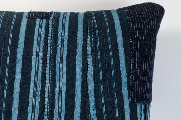 Pillow made using vintage Ashante textile. Handwoven in Nigeria by the Yoruba Tribe. Long strips of cotton hand woven on narrow backstrap looms.  Blue linen back, invisible zipper closure and feather and down fill.