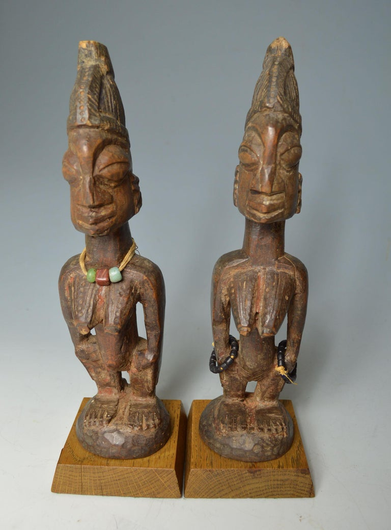 A fine pair of ere Ibeji figures from Ogbomoso Oyo region Nigeria  A pair of hard wood female Ibeji with crest hair style  Showing fine aged patina with camwood powder libation encrustation   Fine carvings from early 20th century  Measure:
