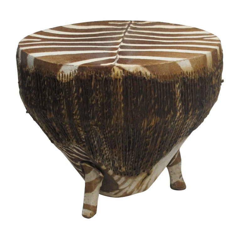Zebra hide stretched over wooden drum with twisted rawhide around the sides standing on three zebra covered legs, African, early 20th century.