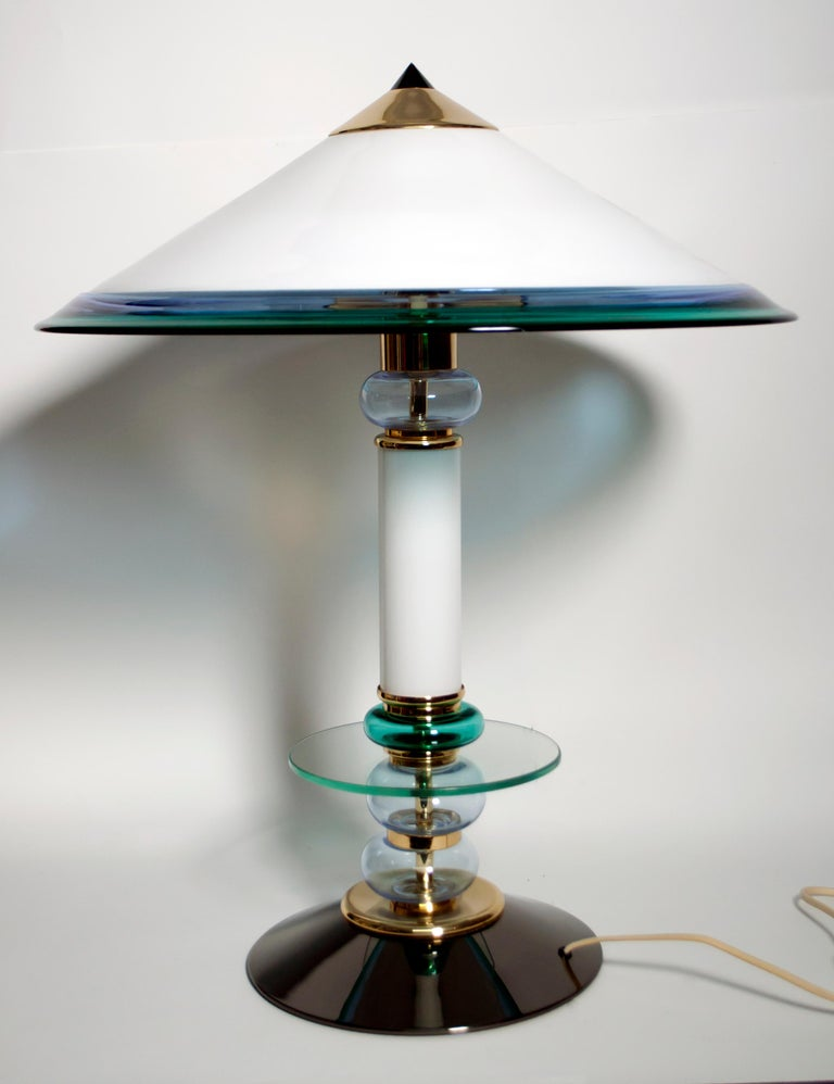 This Murano glass lamp, produced in the 1980s, has a gun metal base and brass parts. It was designed in the style of Ettore Sottsass.