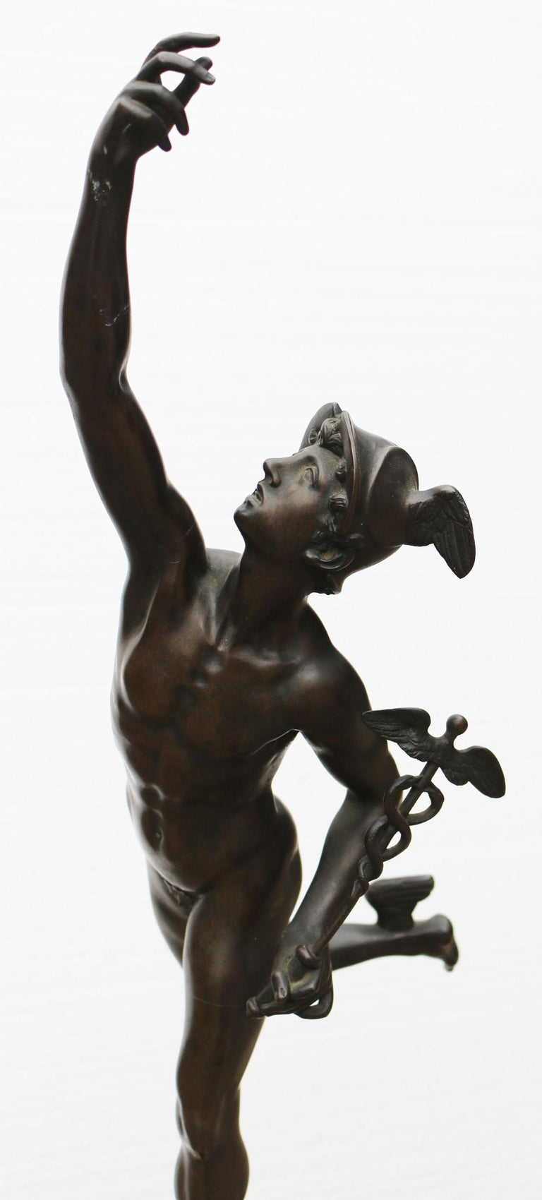 About  A stunning bronze figure of Mercury, holding a Caduceus standing upon the breath of a Nimbus, on a circular base stamped, Jean De Bologne. French or Italian, Circa 1900.   Condition report:  There is no damage to the statue, in very