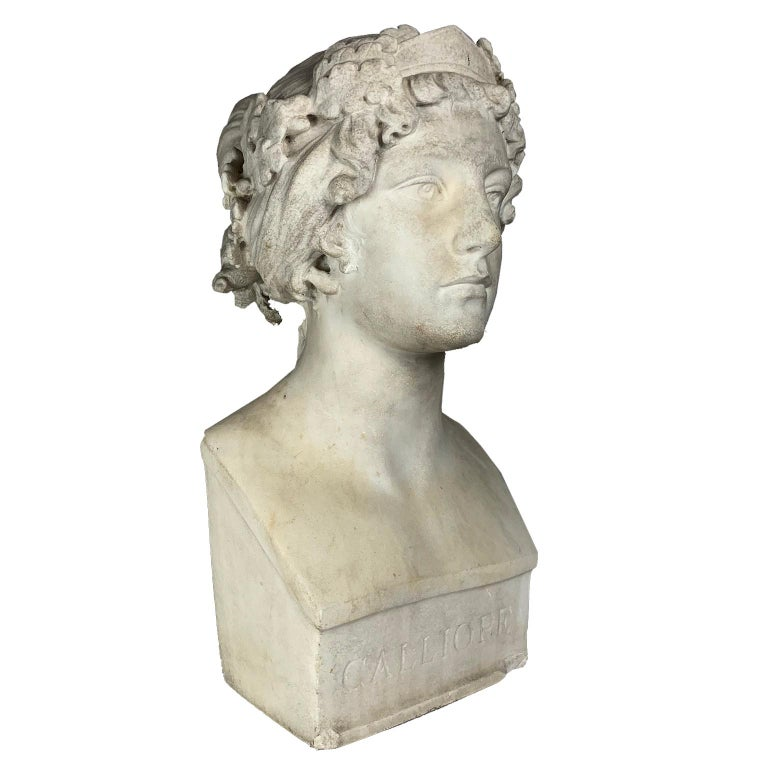 After the Greek Archaic (possibly American sculptor, late 19th-early 20th century) carved white marble bust of the Muse Calliope. Title carved into front base, unsigned. Height: 18 in.   Note: In Greek mythology, Calliope is the muse who presides