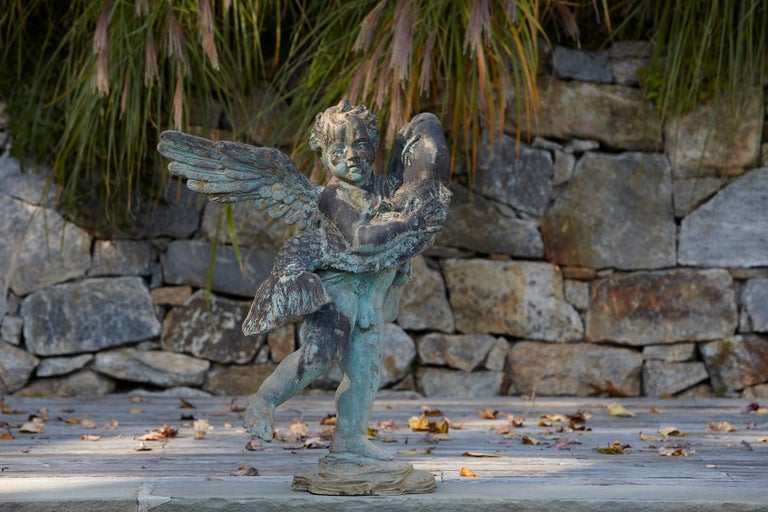 After Andrea del Verrocchio, a beautifully detailed bronze water garden/fountain statue of a cherub with large wings holding a fish in his arms, circa 1940s. The statue has a wonderful, lovely green patina. The statue is piped.