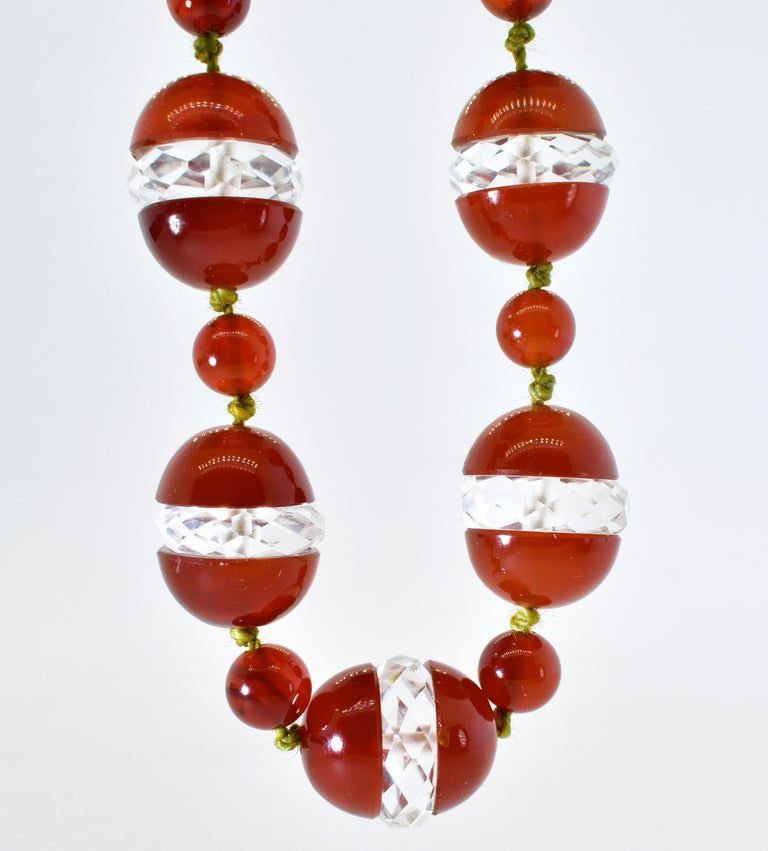 Agate, red/orange in color, round and double cabochon split with natural faceted rock crystal roundels set in between.  The natural agate and rock crystal elements range in size from 11.0  up to 13.25 mm.  This unusual necklace is 17.5 inches long